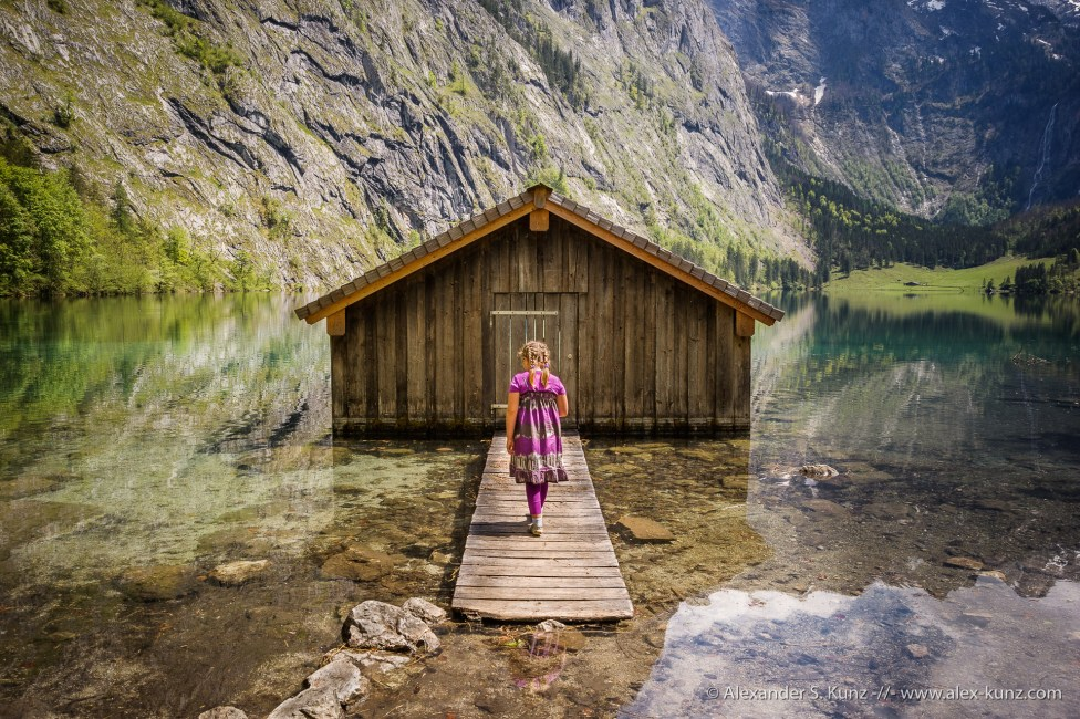 Girl and a boat house at Königssee-Obersee, Nationalpark Berchtesgaden, Bavaria, Germany.