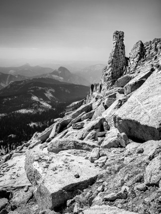 High contrast black & white photo of a rock tower near the peak of Mount Hoffmann, with Half Dome in distant haze. Yosemite National Park, California. September 2015.