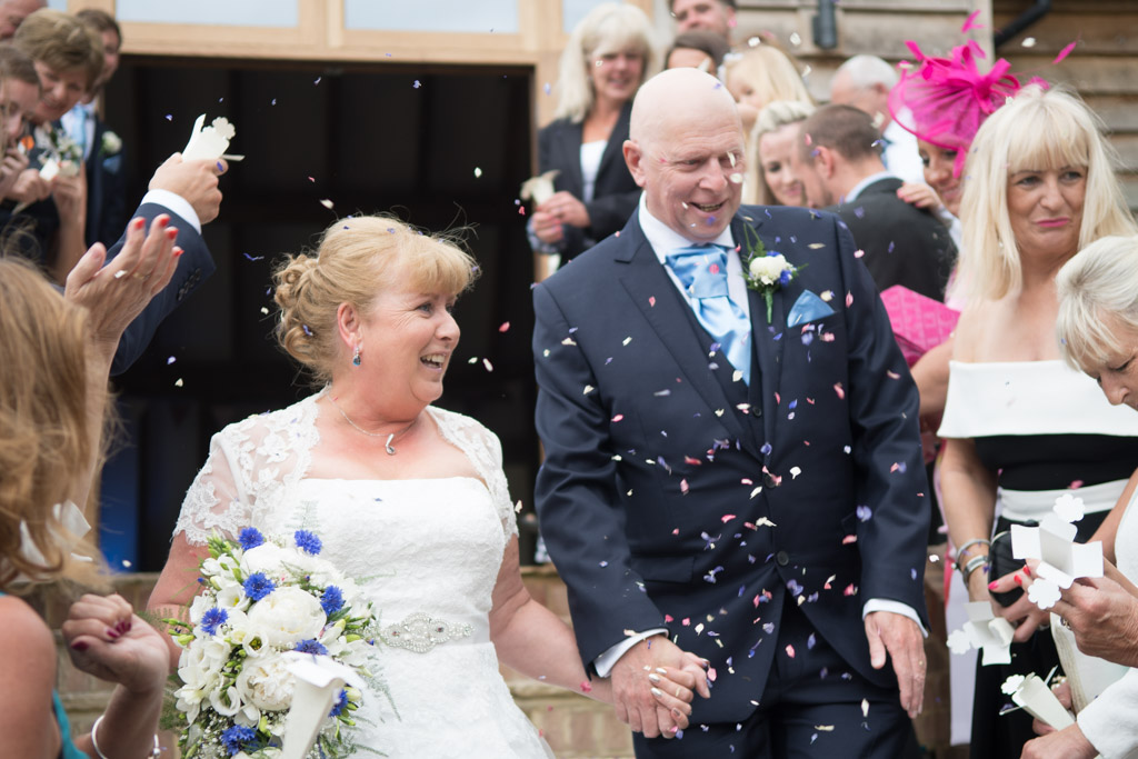 Wedding photo at Brookfield Barn with couple coming through confetti thrown by their guests