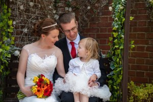 wedding photo of bride and groom talking with their daughter