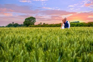wedding photo of the bride and groom out in a field at sunset