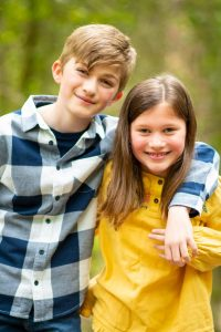 Siblings hugging and smiling at the camera on an outdoor family photo shoot