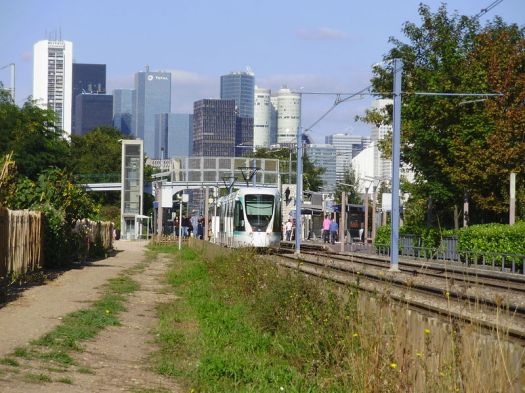T2 at the Belvedere station. Note the alingment within the old rail right of way; La Defense skyscrapers in the background. CC image from Wiki.