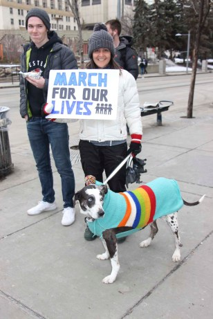 American Sarah Flynn and her dog Cocoa, protesting gun violence in her home country at the Calgary March For Our Lives rally. She said she has been involved in the cause since the Columbine High School shooting in 1999. (Alex Hamilton/SAIT.)