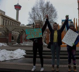 Three young anti-gun violence protesters pose in Olympic Plaza in downtown Calgary, during a March For Our Lives protest on March 24, 2018. The protest against American gun violence was one of over 800 across North America that day. (Alex Hamilton/SAIT.)