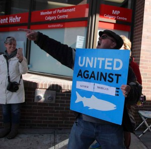 An anti-Kinder Morgan pipeline protestor shouts and points at one of his opponents during a rally on March 23, 2018 at MP Kent Hehr's office. He appears to have reused a sign from a previous protest. (Alex Hamilton/SAIT.)