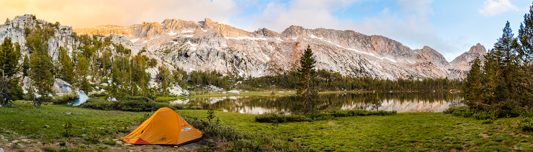 A single orange tent among beautiful granite mountains and small lake at sunset.