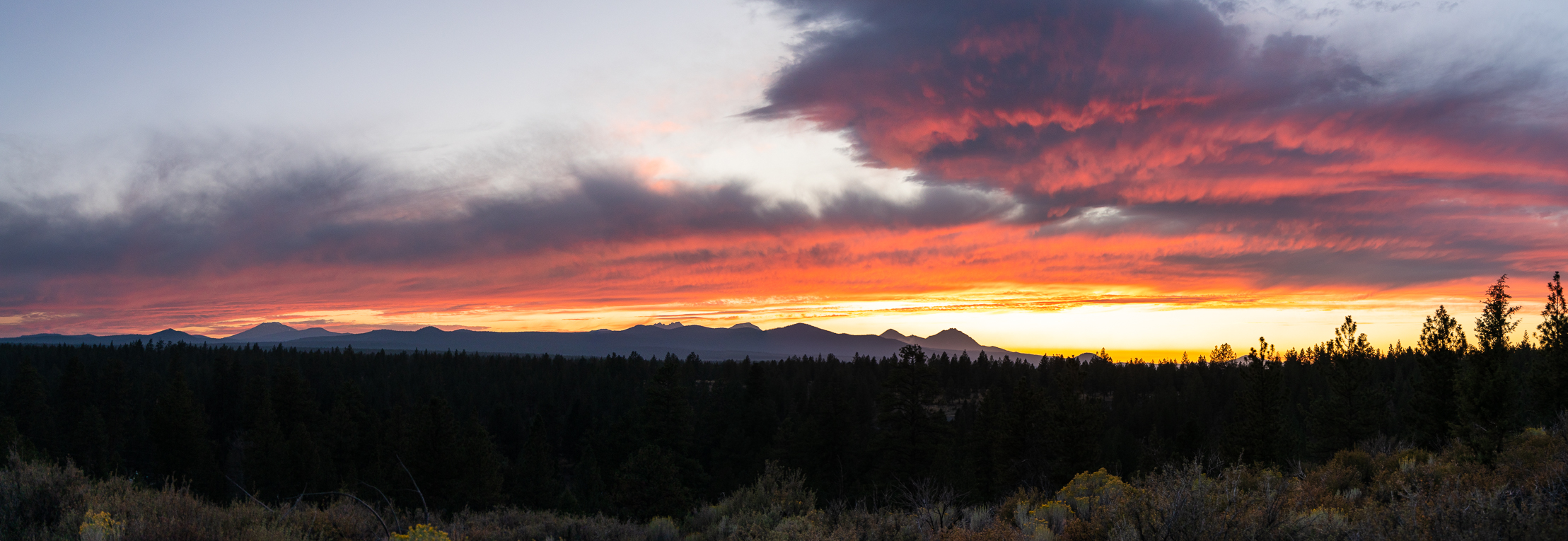 Panorama of Cascade Mountain Wilderness with Broken Top, Three Sisters and other peaks in view at sunset.
