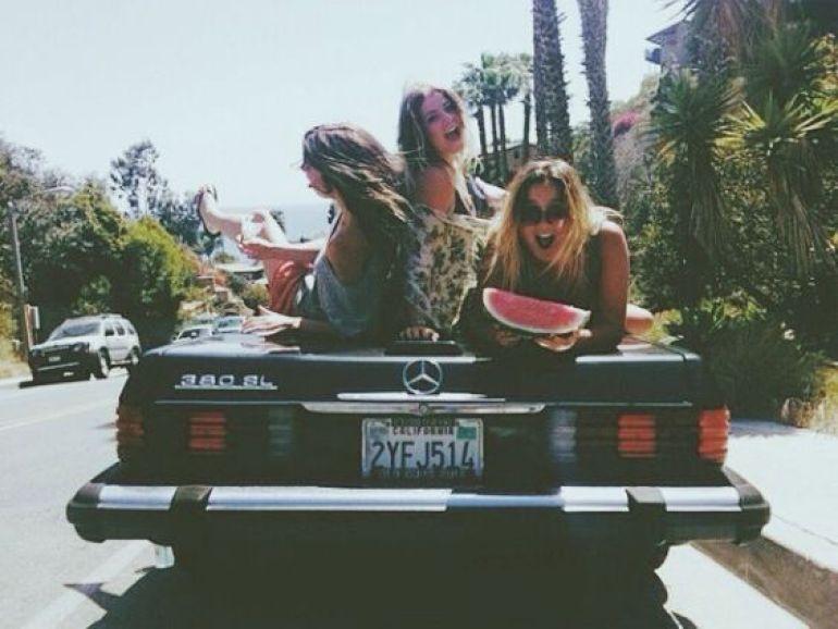 Girls sitting on the back of a car having fun