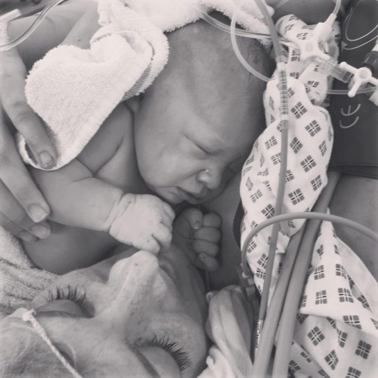 Mother holding her daughter for the first time post assisted birth