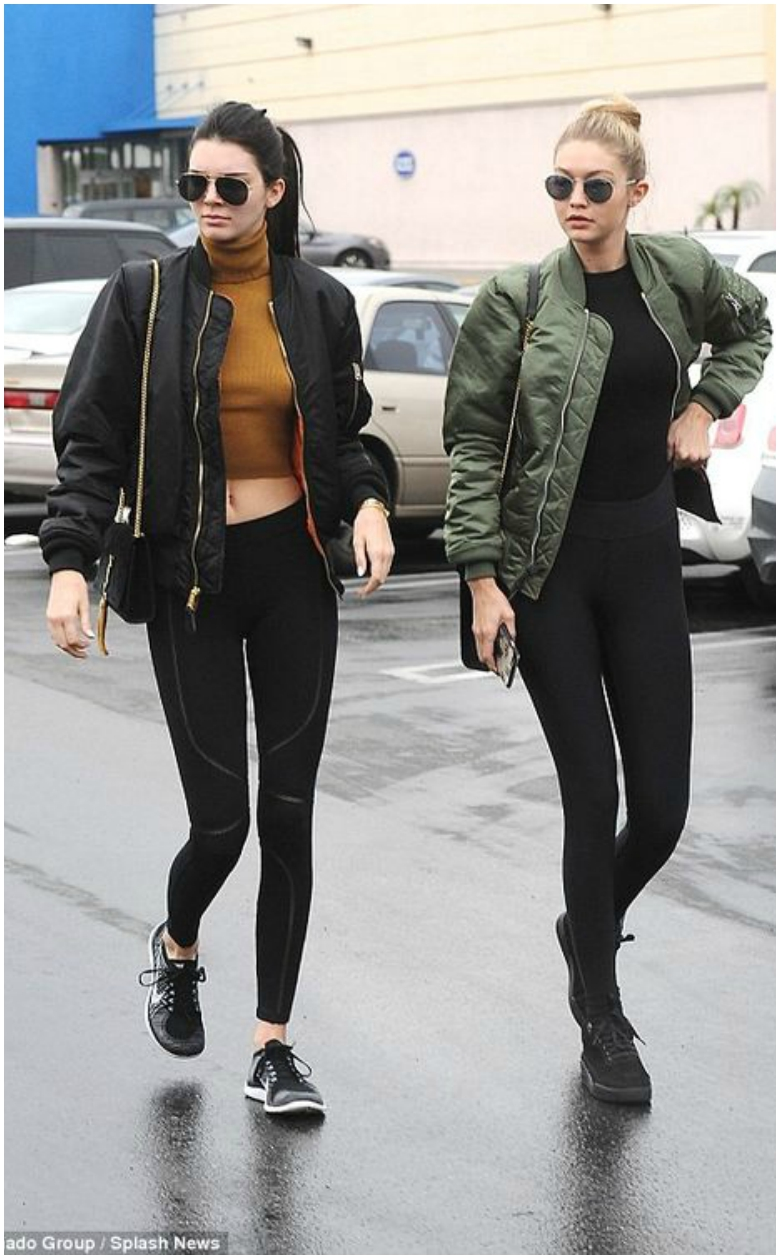 Kendall Jenner in black bomber jacket, crop top and jeans and Gigi Hadid in green bomber jacket with black top and jeans