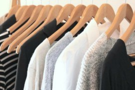A mixture of white, black and grey clothes on hangers