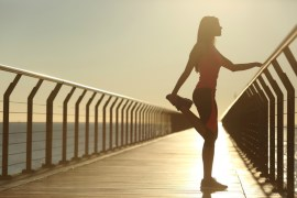 woman in running gear stretching on pier