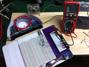 Bulbdial clock with breadboard and multimeter