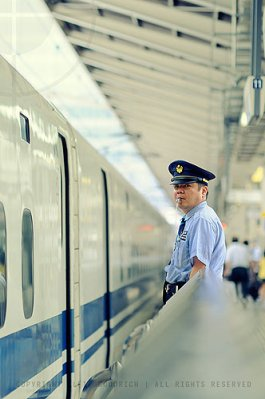 Guard waves out the shinkansen [bullet-train]: Tokyo