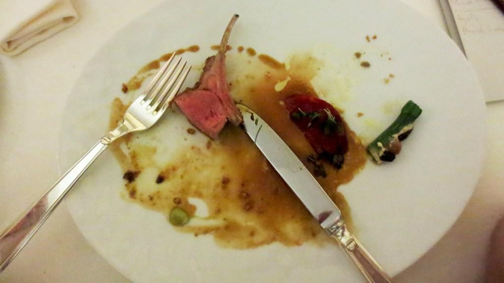 """Carré di agnello in crosta """"Ackermann"""" arrostito sull'osso, variazione di piccole verdure del sud e condimento di harissa verde"""