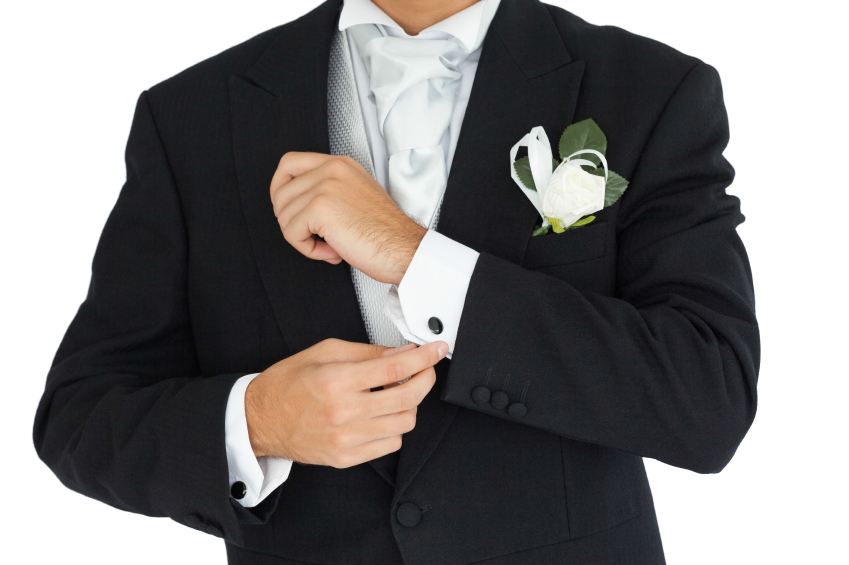 Close up of a smart groom buttoning his cufflinks on white background