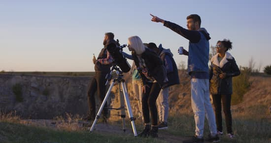 Friends stargazing together using a professional telescope