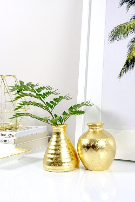 DIY gold leafed vases styled on white credenza with palm tree print