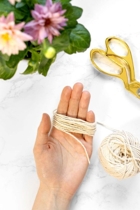 Wrapping cotton string to create a tassel for wood bead garland