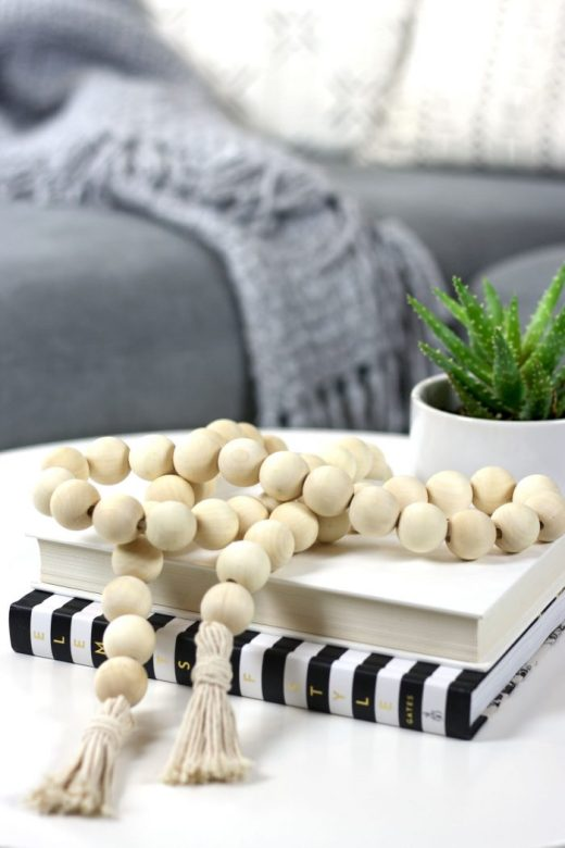 Close up of DIY bohemian wood bead garland styled on IKEA coffee table
