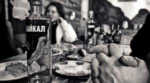 Adult alcohol bar featuring rusian vodka botthe in front and beautiful woman in background
