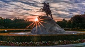 Russian statue of horseman in screen center at beautiful sunset in park