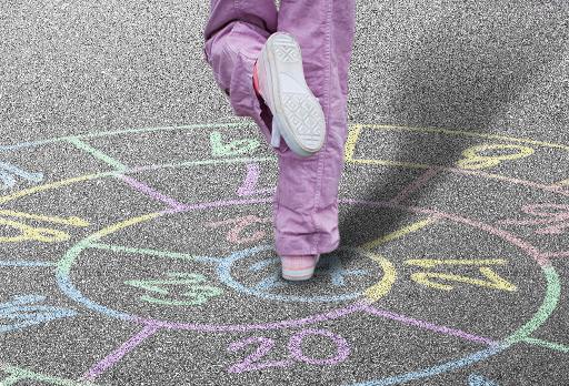 Grupo de crianças a brincar ao Jogo do Caracol, com o caracol desenhado no chão.