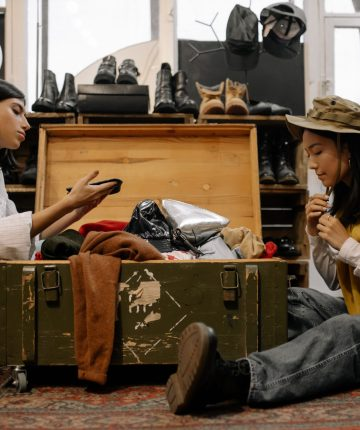 shoppers looking through thrift store clothes