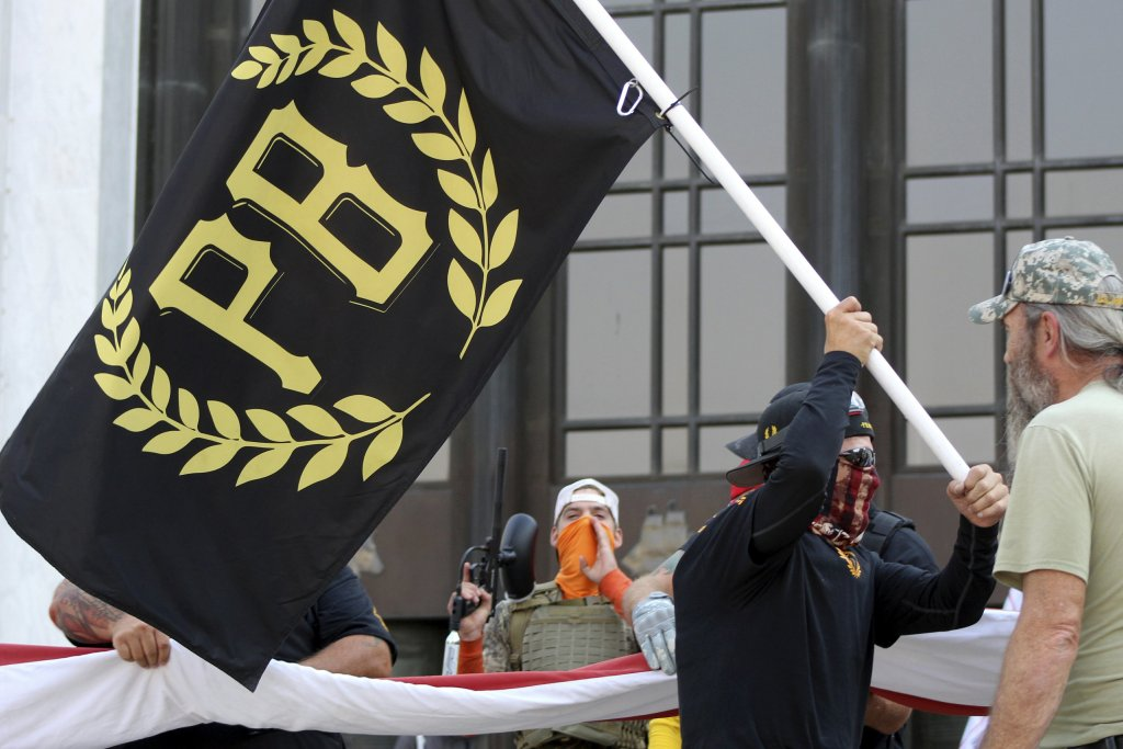 man waving proud boys flag
