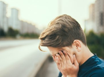 tired man rubbing eyes on street