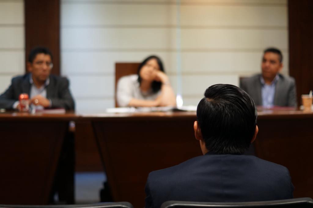 man sitting before panel of judges