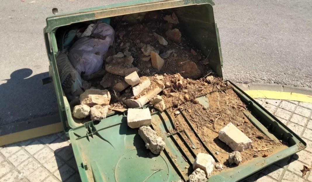 Escombros en un contendor volcado en Umbrete.