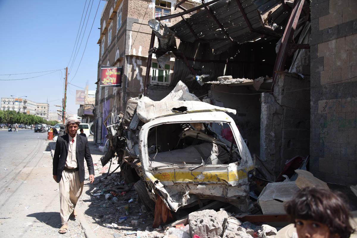A man walks by civilian houses destroyed in Sanaa. [Karl Schembri/NRC/Al Jazeera]