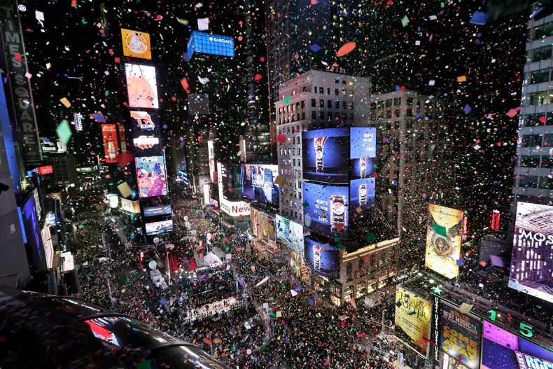 Confetti drops over the crowd as the clock strikes midnight during New Year's Eve celebrations in Times Square. [Seth Wenig/AP  Photo]