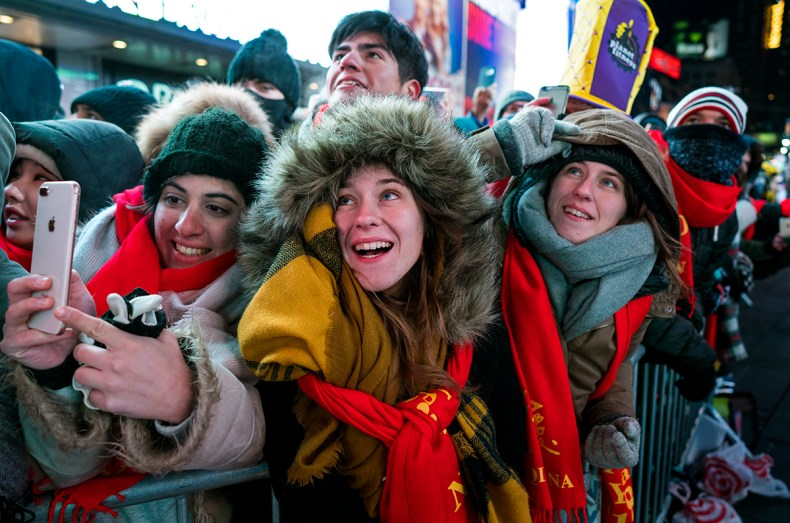 Revelers gather at Times Square in New York to watch the ceremonial ball rise to the top of a pole high above the street in preparation for the ball drop during New Year's Eve celebrations. [Craig Ruttle/AP Photo]