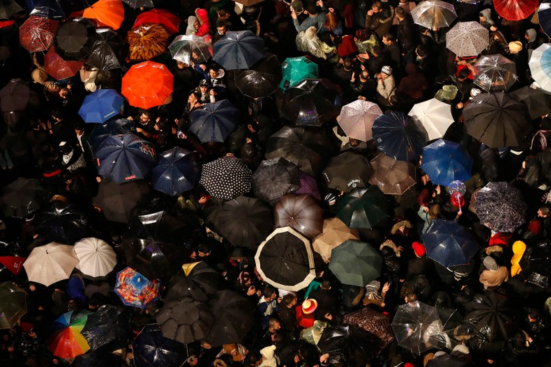 Revelers hold their umbrellas during New Year's Eve celebrations at Parliament Square in downtown Beirut, Lebanon. [Hussein Malla/AP Photo]