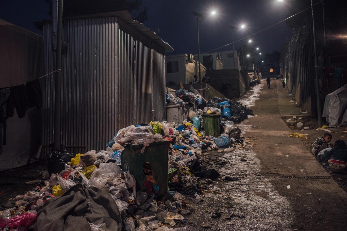 Σωροί αποβλήτων διαδίδονται σε όλο το στρατόπεδο.  Οι κάτοικοι κατηγορούν τις αρχές ότι δεν καθαρίζουν τις καθορισμένες περιοχές κάθε εβδομάδα.  Εκτιμάται ότι ο στρατόπεδο Moria φιλοξενεί πάνω από 2,5 φορές περισσότερα άτομα από την προβλεπόμενη χωρητικότητά του.  [Kevin McElvaney / Al Jazeera]