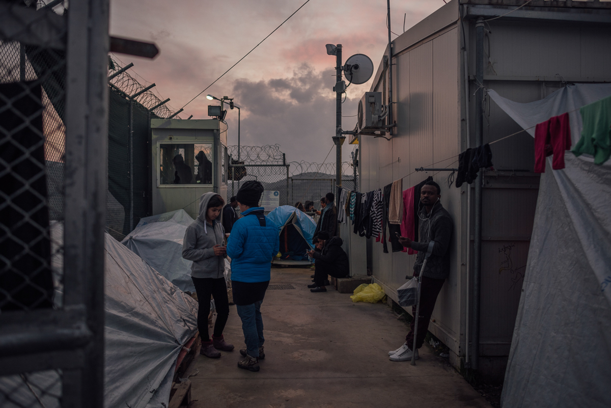 Οι αιτούντες άσυλο συγκεντρώνονται γύρω από το μοναδικό wifi-hotspot στο στρατόπεδο Moria.  Μόνο με περιπτώσεις έκτακτης ανάγκης που επιτρέπεται να ταξιδεύουν στην ηπειρωτική Ελλάδα, όπου οι συνθήκες είναι γενικά καλύτερες, πολλοί πρέπει να περιμένουν περισσότερους από 12 μήνες μέχρι να διεκπεραιωθούν οι αξιώσεις τους.  [Kevin McElvaney / Al Jazeera]