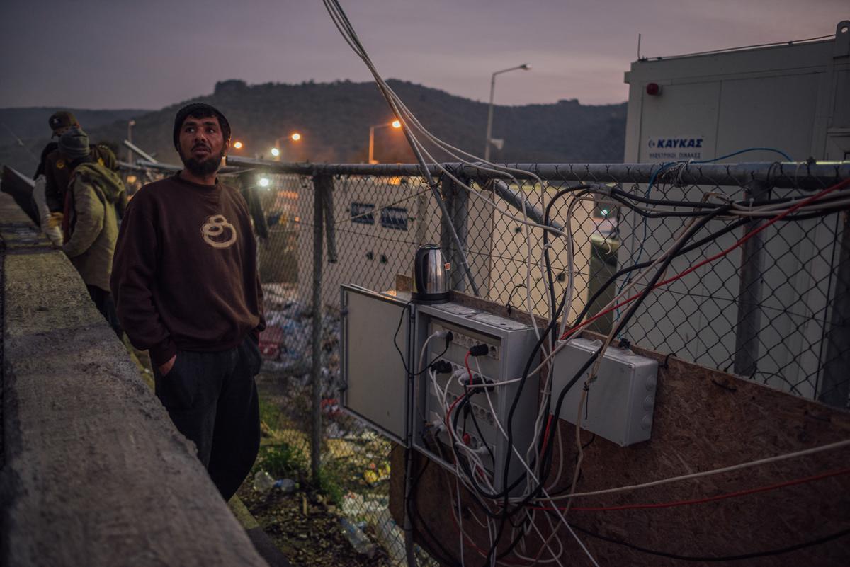 Ένας αιτών άσυλο κάνει το τσάι σε ένα από τα σπάνια λειτουργικά σημεία ηλεκτρικής ενέργειας του στρατοπέδου.  Το δίκτυο συχνά καταρρέει και οι άνθρωποι δεν έχουν πρόσβαση στην εξουσία για μέρες.  [Kevin McElvaney / Al Jazeera]
