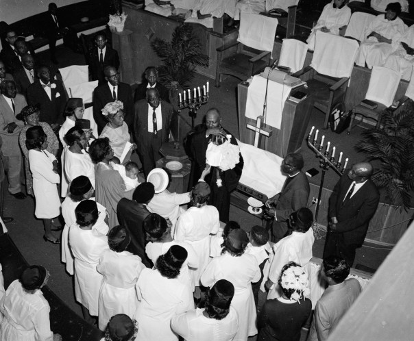 A minister baptises a child at Allen Chapel in Fort Worth on Easter Sunday in 1969. Calvin Littlejohn was everywhere - he had to be for his photography studio work and occasional freelance photography for local newspapers. Although he never set out to be the documentarian of Fort Worth's Black community, that's what he achieved by striving to capture the best of a community. [Calvin Littlejohn; Calvin Littlejohn Photographic Archive, Briscoe Center for American History]