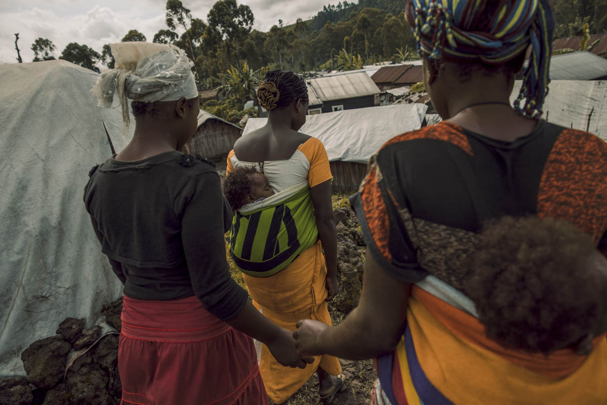 Three survivors of sexual assault walk through a camp for people displaced by the conflict in North Kivu, eastern DR Congo. [Hugh Kinsella Cunningham/Save the Children]