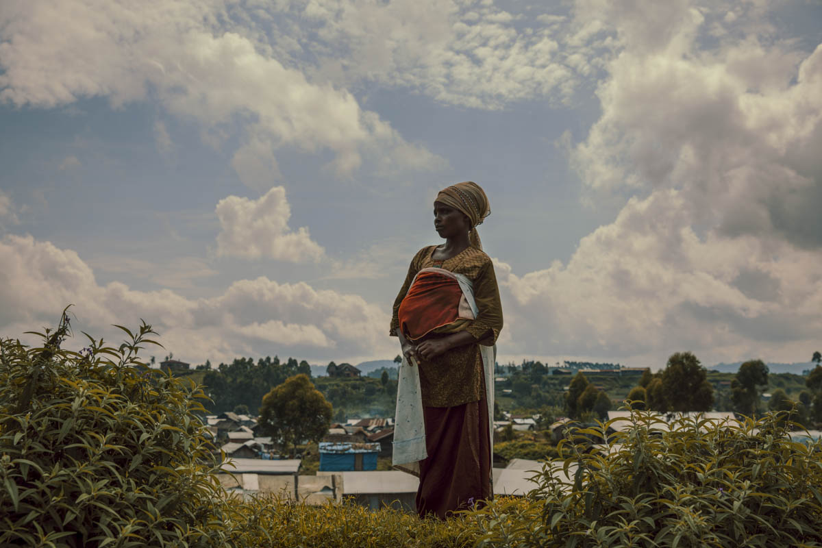Alphonsine and her baby wait outside a Save the Children health clinic in a camp for communities displaced by conflict. [Hugh Kinsella Cunningham/Save the Children]