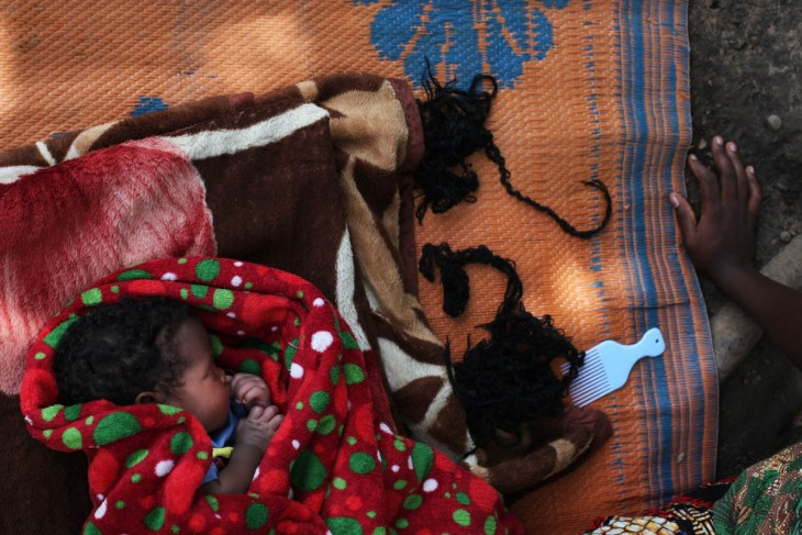 The one-month-old baby girl of a mother, 16, who was held by rebel soldiers, is sleeping on a mat in their compound, outside Yambio. The mother was made a second wife for one of the soldiers, but other men were sleeping with her, too. She does not know who the father is, but she loves the child. 'My grand-mother welcomed me when I came back, and the child when she was born. But some neighbours were scared. They said I had the mindset of the people in the bush. I was made to kill and maybe I would do it again.' She's learning tailoring but after, would like to go back to primary school. She says till today, she doesn't dare to go back to the fields because she is scared of being abducted again. [Andreea Campeanu/Al Jazeera]