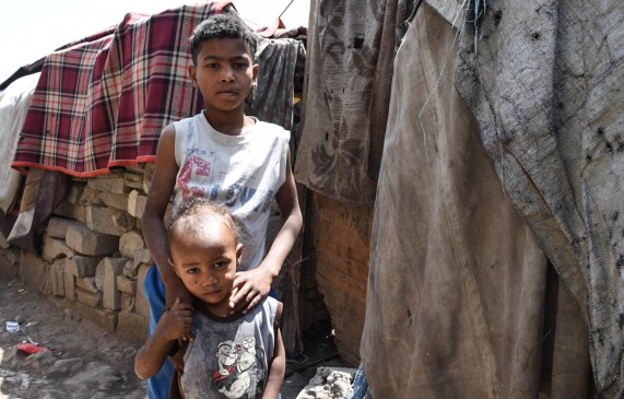 Abdullah, 8, and his brother Hussein, 2, in front of their shelter in a camp for displaced people in Sana'a city. Abdullah joins his father each day as they try to eke out a living in their new surroundings. 'I spend my days collecting plastic jerry cans for water. Every morning I collect them and try to sell them,' says Abdullah. [Becky Bakr Abdulla/Norwegian Refugee Council]