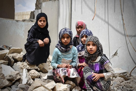 A group of young girls sits in the rubble of their school in Amran city. The school had been open for only a year before it was struck by an air attack in 2017. Two thousand children were left without education as a result. [Suze van Meegen/Norwegian Refugee Council]