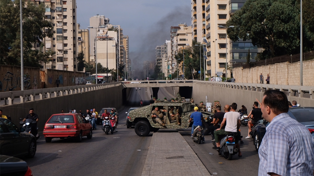 A convoy of Army Humvees turns around after being confronted by protestors at a roadblock oustide central Beirut [Timour Azhari/Al Jazeera]