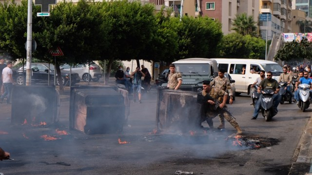 A soldier tried to clear a path through smoldering garbage bins and flaming tires on the outskirts of downtown Beirut [Timour Azhari/Al Jazeera]