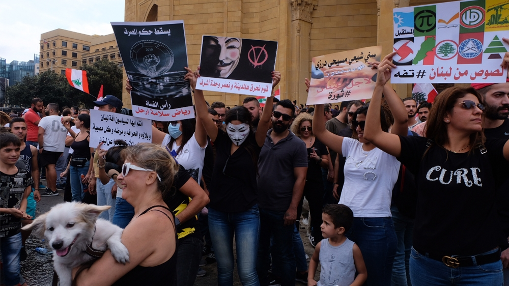 Protestors hold placards calling out the political establishment in downtown Beirut  [Timour Azhari/Al Jazeera]