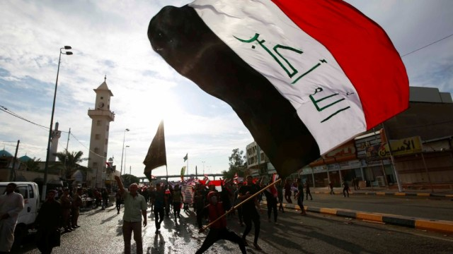 A demonstrator holds an Iraqi flag during a protest over corruption, lack of jobs, and poor services, in Najaf, Iraq October 25, 2019